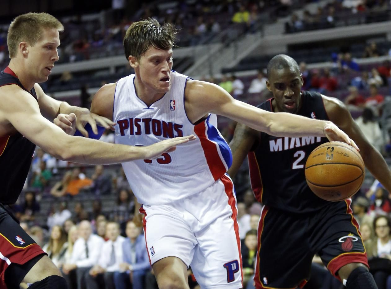 Detroit Pistons forward Jonas Jerebko, center, of Sweden, tries to maintain control of the ball against Miami Heat center Justin Hamilton, left, and Jarvis...