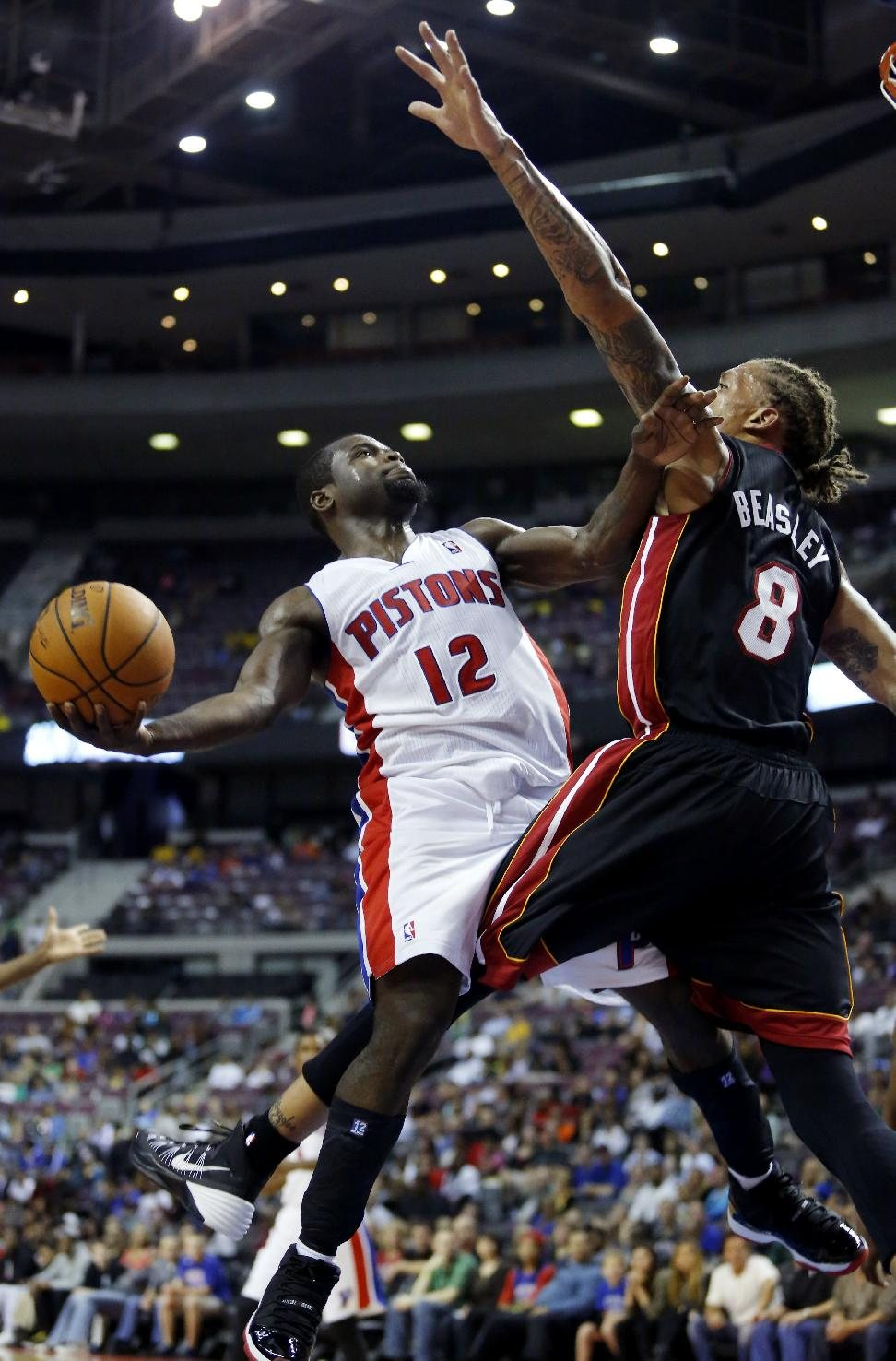 Detroit Pistons guard Will Bynum (12) goes to the basket against Miami Heat forward Michael Beasley (8) in the second half of a preseason NBA basketball...
