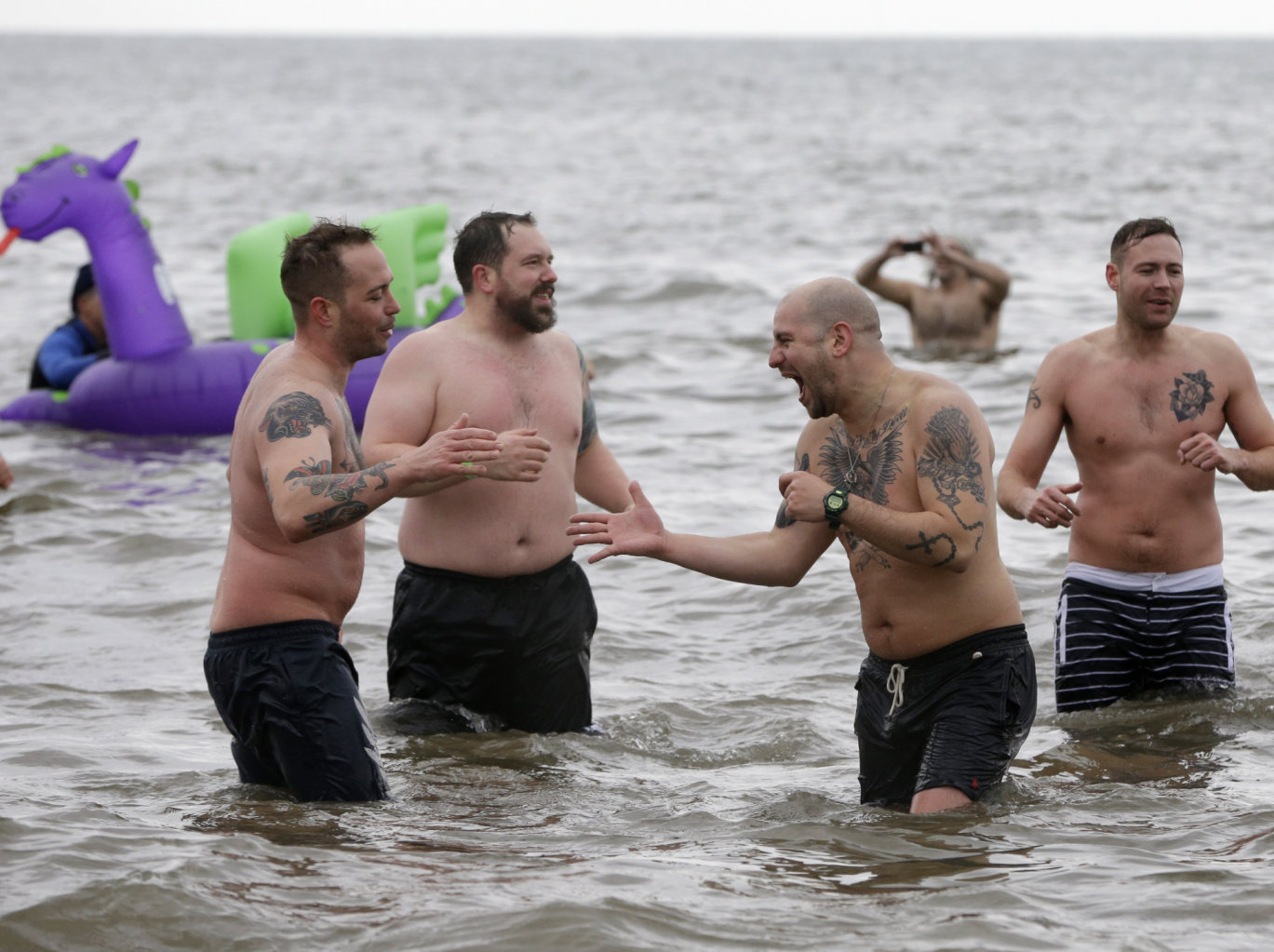 Tattooed men congratulate each other on taking the plunge during the 110th annual Coney Island Polar Bear Club ocean swim at Coney Island in New York,