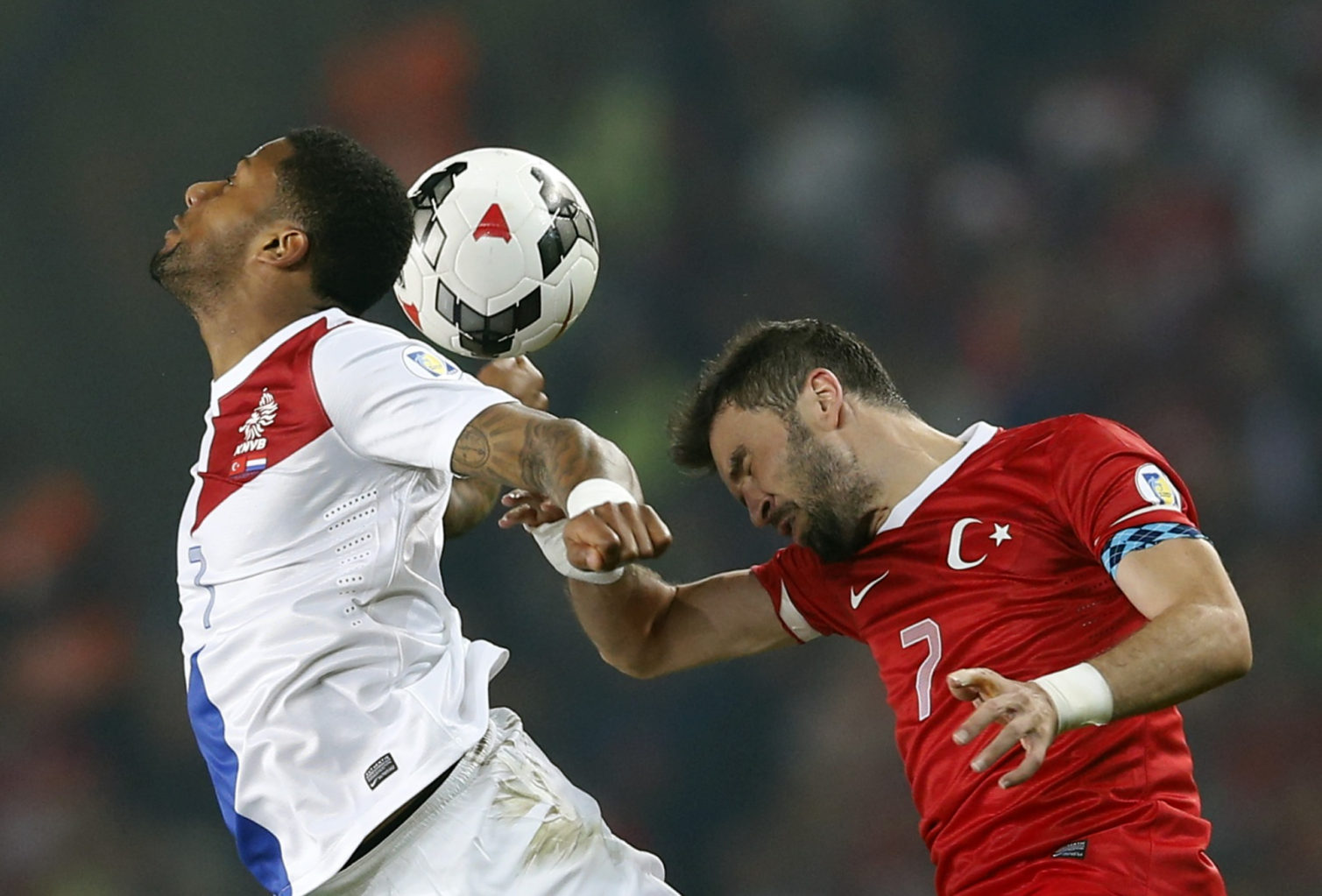 Netherlands' Lens and Turkey's Gonul jump for header during 2014 World Cup qualifying soccer match in Istanbul