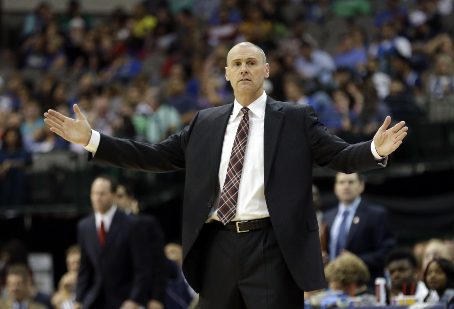 Dallas Mavericks head coach Rick Carlisle opens his arms while coaching from the sideline during the first half of an NBA preseason basketball game against...